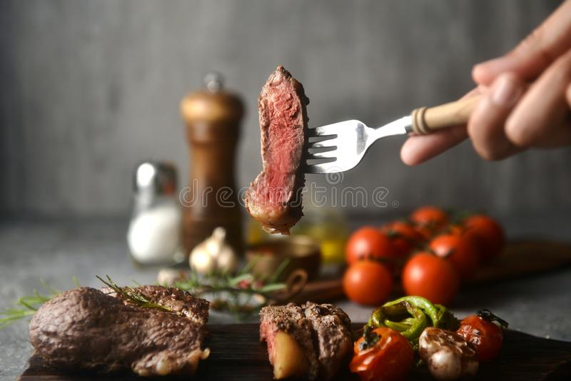 Pezzi della bistecca su una forcella che tiene a mano, circondato dagli ingredienti di condimento, immagine orizzontale fotografie stock
