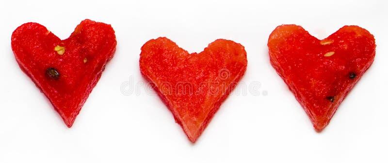 Pezzi di anguria nella forma di cuore isolata sul backgro bianco fotografia stock