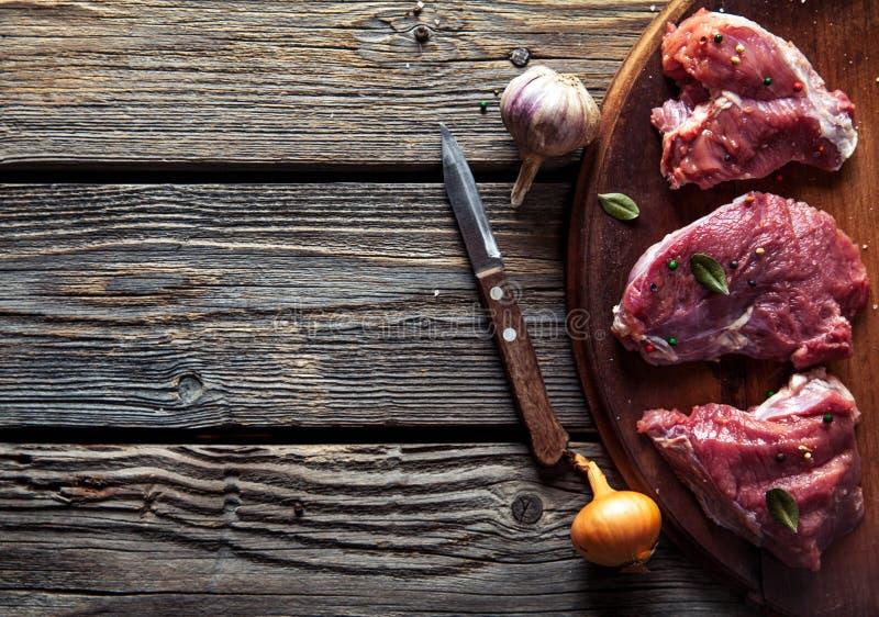Pezzi di carne, bistecca con le spezie su un fondo di legno Alimento immagini stock libere da diritti