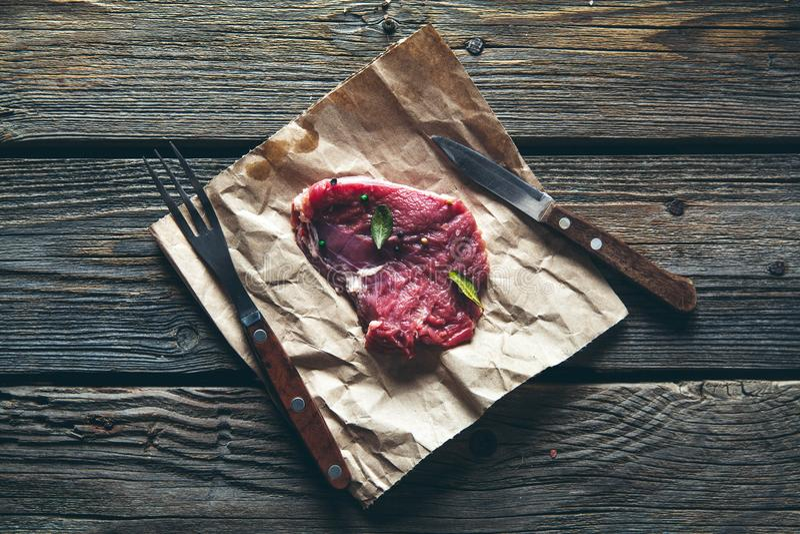Pezzi di carne, bistecca con le spezie su un fondo di legno Alimento fotografie stock libere da diritti