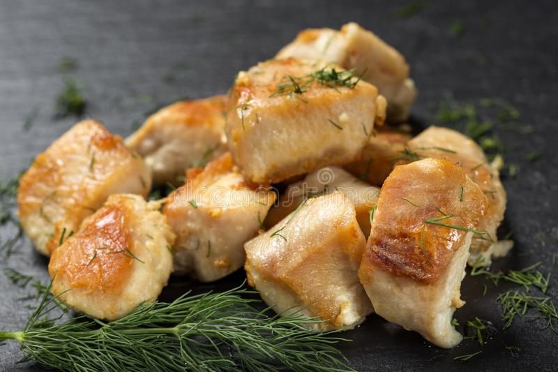 Pezzi di carne del seno di pollo fritto su un'ardesia scura con la d verde immagine stock libera da diritti