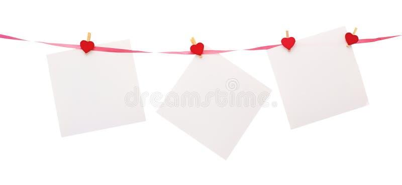 Pezzi di carta con il clothespin a forma di del cuore immagini stock libere da diritti