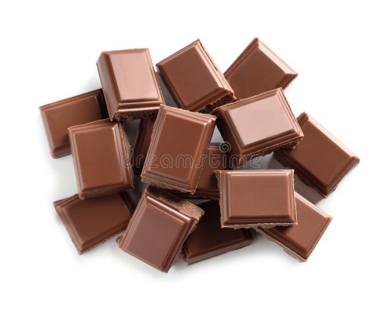 Pezzi di cioccolato al latte saporito su fondo bianco fotografia stock