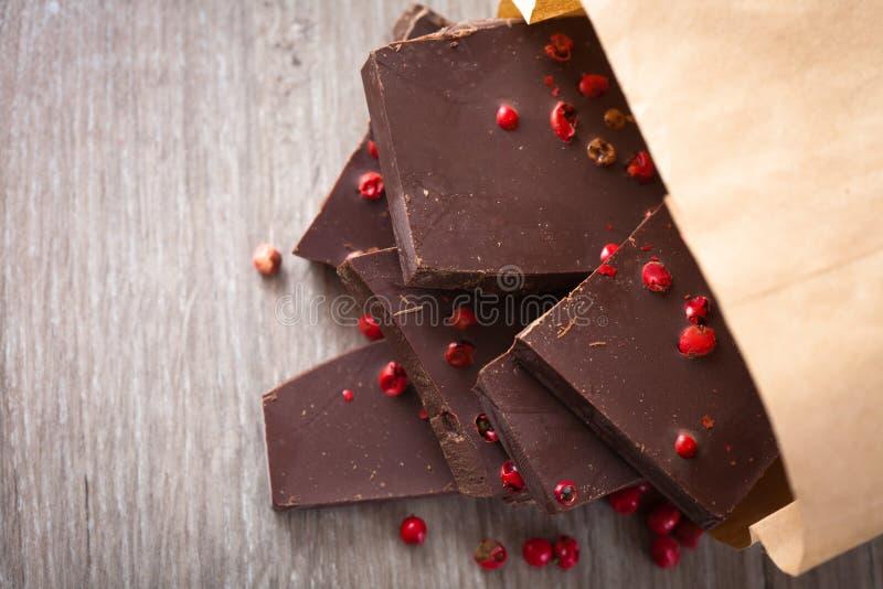 Pezzi di cioccolato fondente con pepe rosa immagine stock