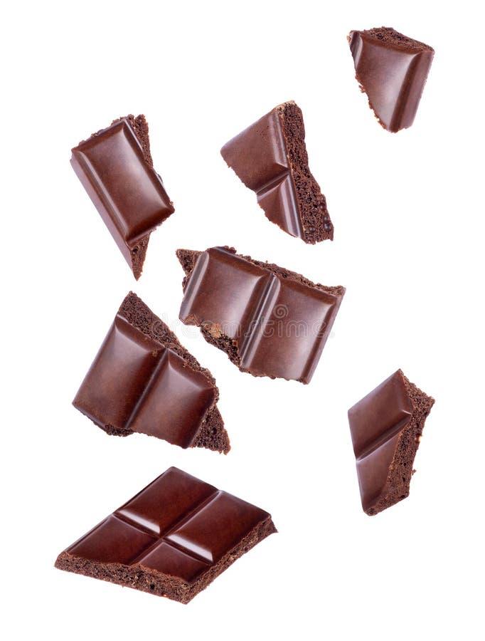 Pezzi di cioccolato poroso che cadono vicino su su un bianco fotografia stock