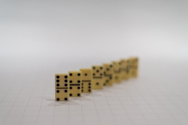 Pezzi di domino nella fila con prima una messa a fuoco immagini stock libere da diritti
