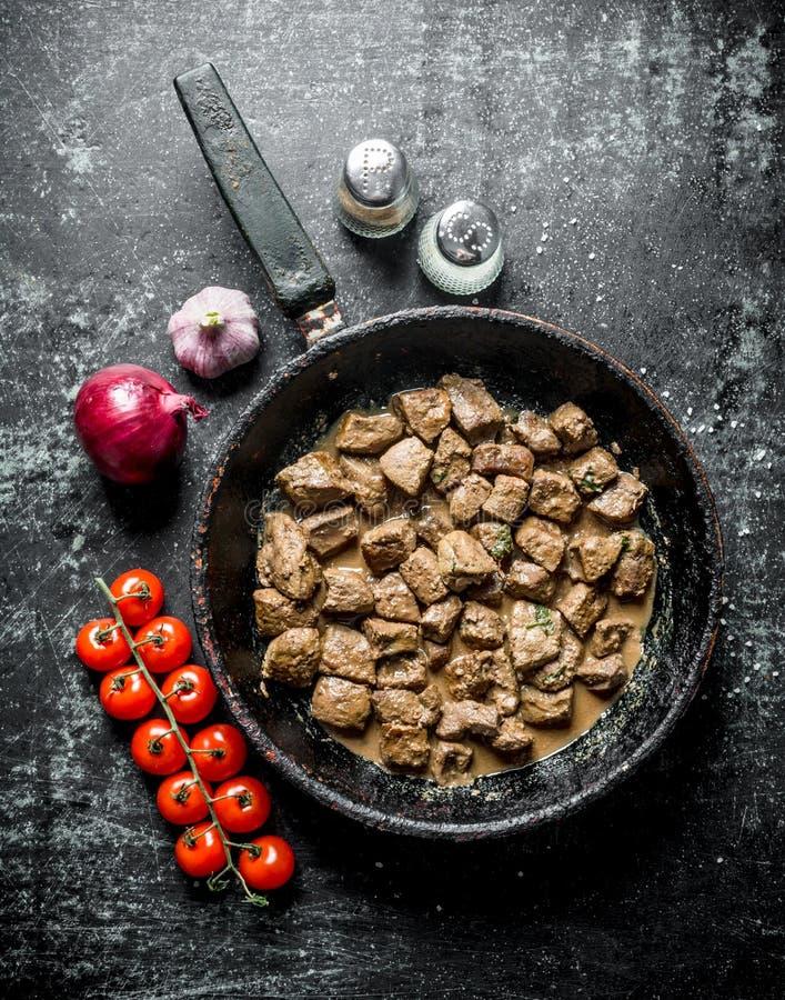 Pezzi di fegato fritto in una pentola con le cipolle, l'aglio ed i pomodori immagini stock