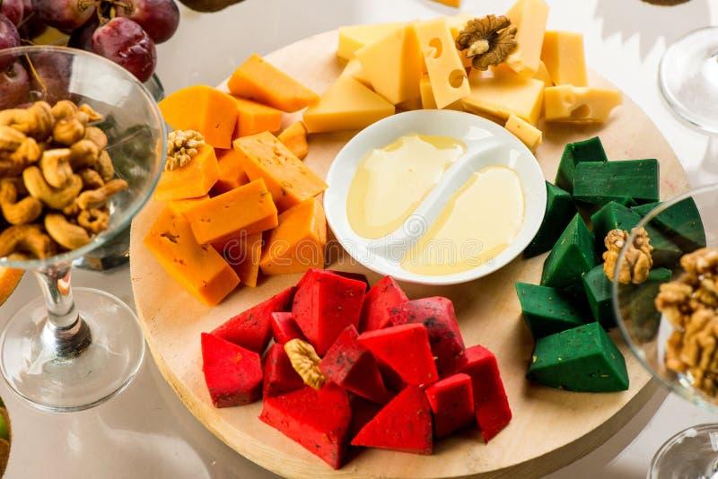 Pezzi di formaggio delle varietà differenti con miele fotografia stock