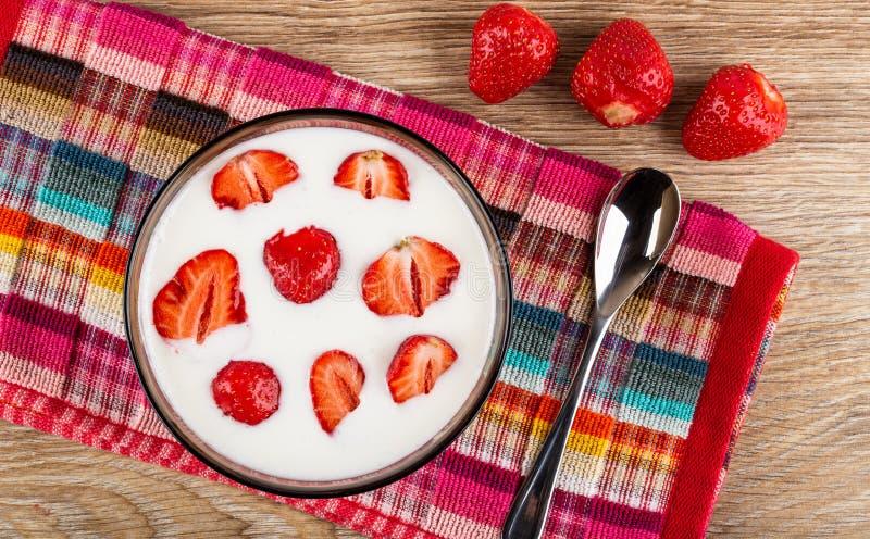 Pezzi di fragole in ciotola con yogurt, cucchiaino sul tovagliolo, bacche sulla tavola di legno Vista superiore fotografie stock