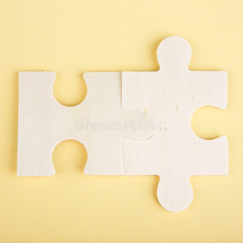 Pezzi di legno di puzzle su un fondo giallo fotografia stock