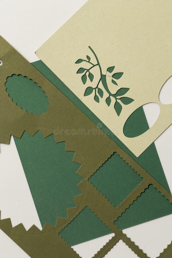 Pezzi di Libri Verde con le figure perforate quadrate e carte rimanenti delle carte perforate immagine stock