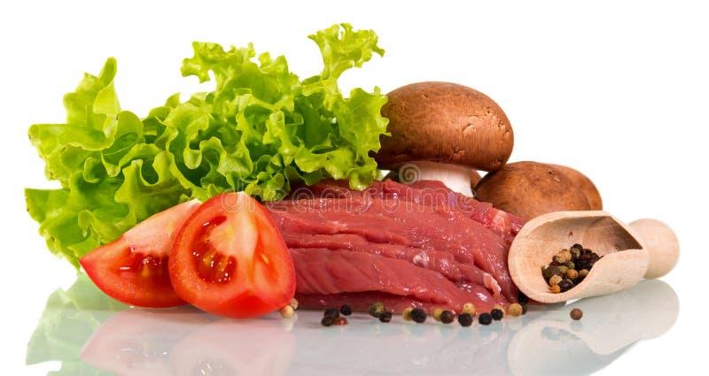 Pezzi di manzo crudo, pezzi del pomodoro, funghi, lattuga e mestolo fotografia stock