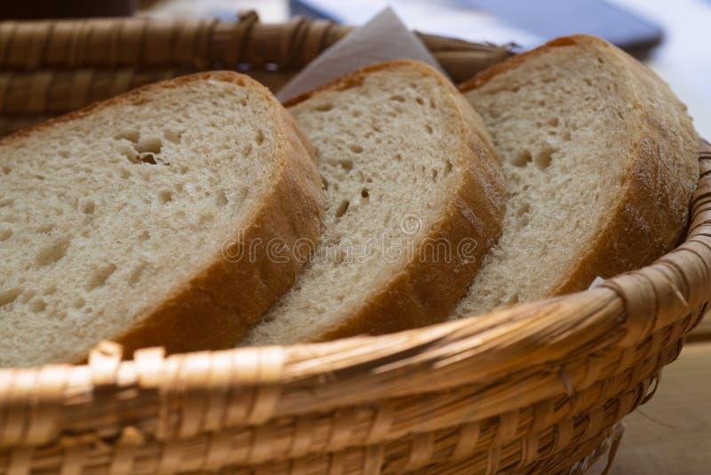 Pezzi di pane in canestro di vimini sulla tavola di legno fotografia stock libera da diritti