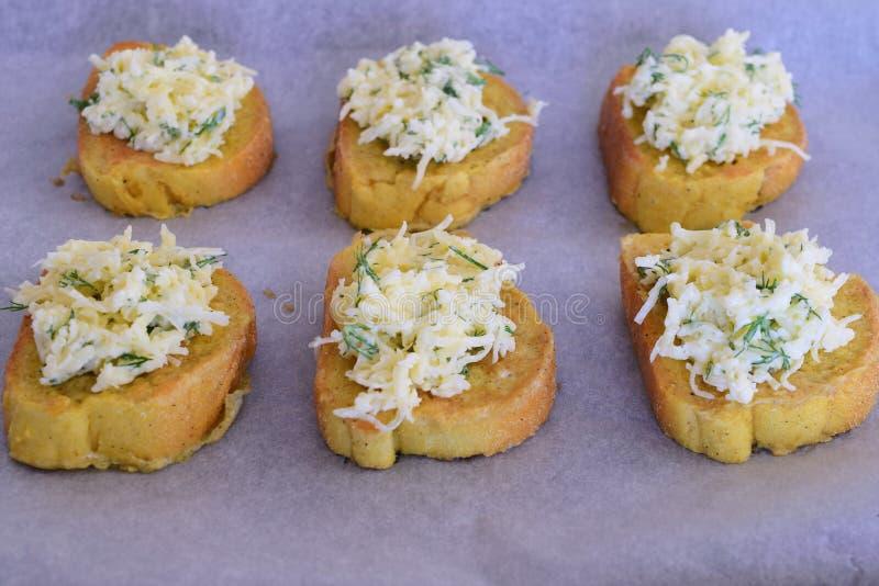 Pezzi di pane tostato con formaggio, erbe e guarnizione fresche dell'aglio fotografie stock libere da diritti