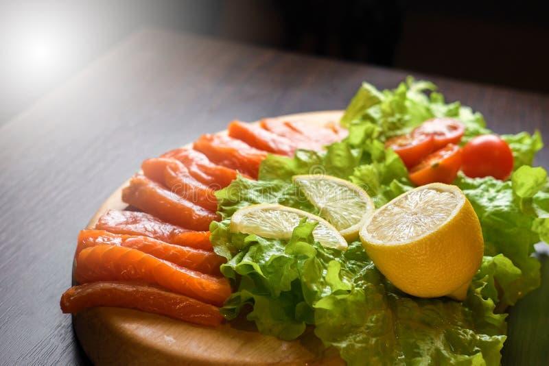 Pezzi di pesce rosso con il limone ed i pomodori ciliegia su un bordo di legno fotografia stock libera da diritti