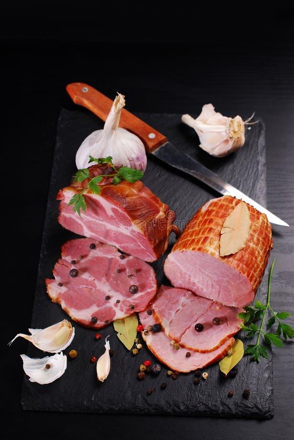 Pezzi di prosciutto affumicato casalingo della carne di maiale su fondo nero immagine stock libera da diritti