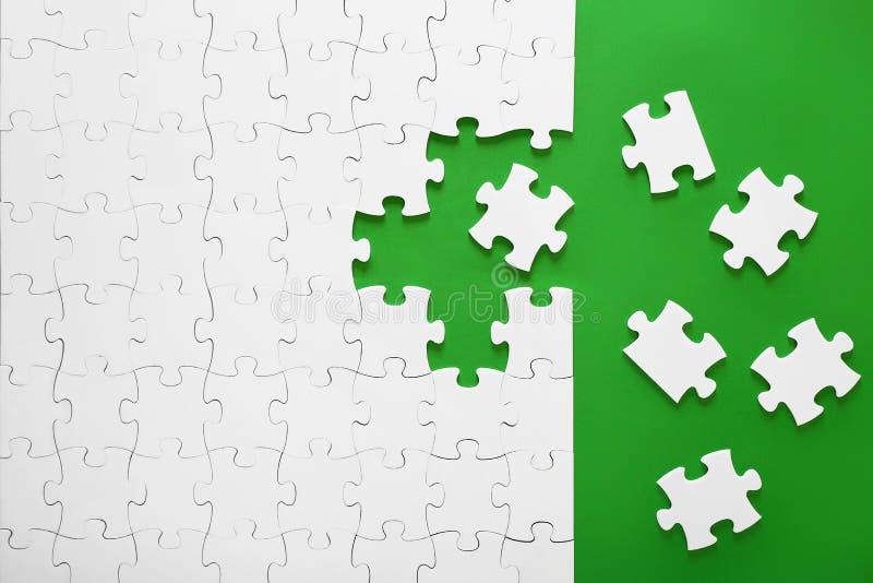 Pezzi di puzzle su un fondo verde immagini stock