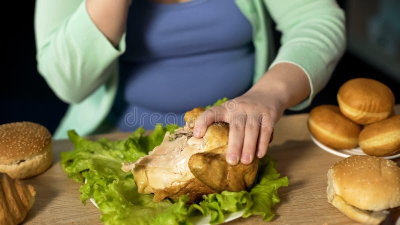 Pezzi di signora obesa di carne strappanti fuori da disordine digestivo degli alimenti industriali del pollo arrosto fotografia stock