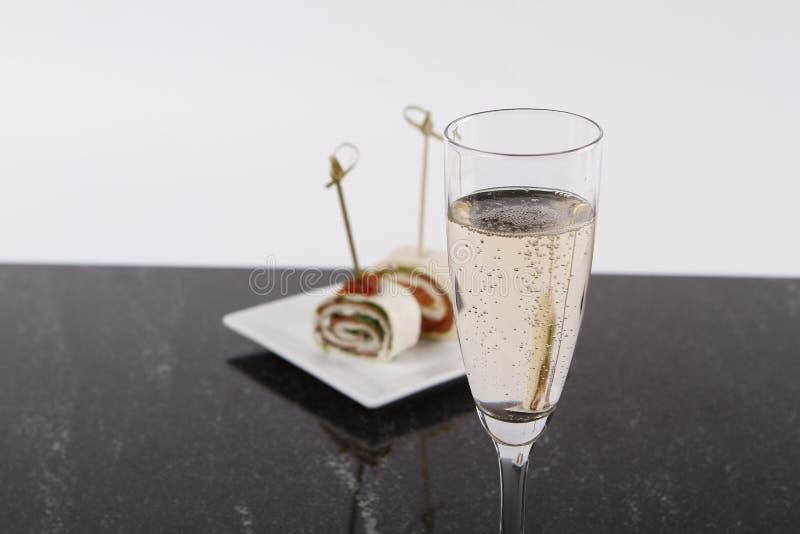 Pezzi di wrappes riempiti e un vetro di champagne fotografia stock libera da diritti