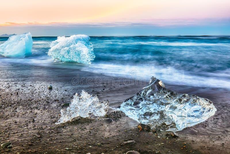 Pezzi incredibili della scintilla dell'iceberg su Diamond Beach famoso alla laguna di Jokulsarlon durante il tramonto fotografia stock libera da diritti
