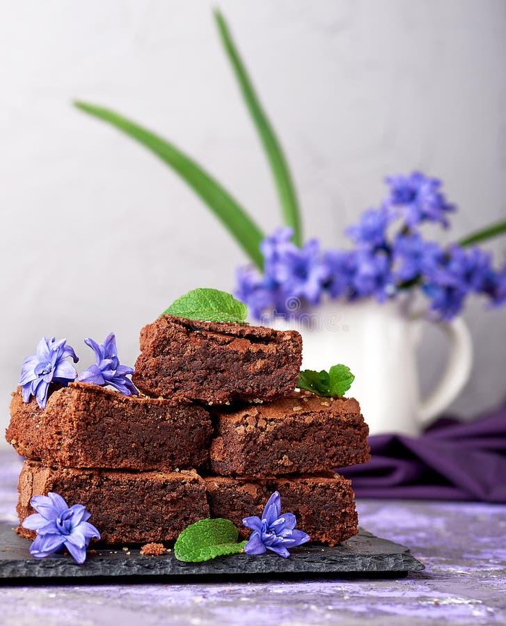 Pezzi quadrati di brownie su un piatto nero della grafite fotografia stock libera da diritti