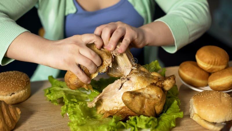 Pezzi strappanti di pollo arrosto, problema di eccesso di cibo, sforzo della donna di peso eccessivo immagine stock
