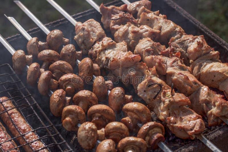 Pezzi succosi di primo piano della carne sulla griglia sugli spiedi accanto ai funghi deliziosi fritti sui carboni immagine stock