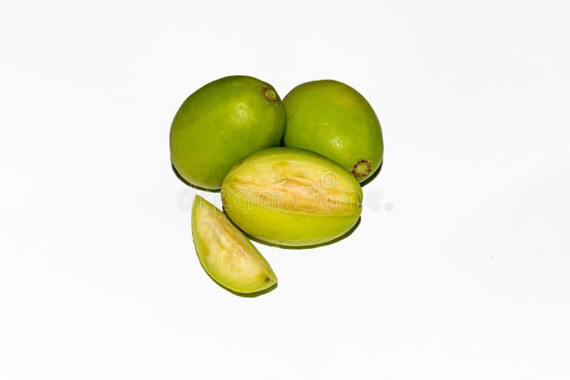 Pezzi tagliati di frutti verdi freschi di spondias dulcis su fondo isolato bianco fotografie stock