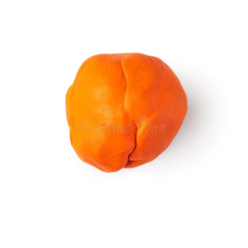 Pezzo arancio di plastica su un fondo bianco fotografia stock