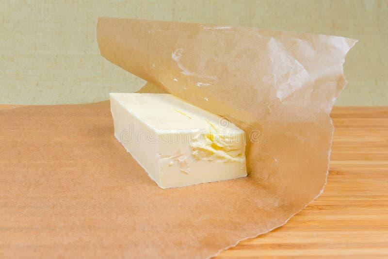 Pezzo di burro solido su carta oleata su superficie di legno fotografie stock
