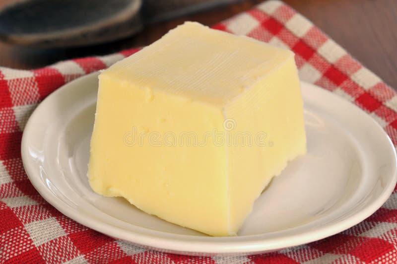 Pezzo di burro in un piattino immagini stock