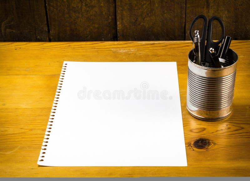 Pezzo di carta in bianco sulla tavola di legno con le penne in latta del metallo fotografia stock libera da diritti
