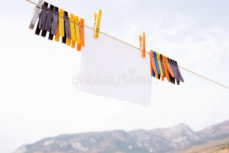Pezzo di carta che appende sul cavo con i clothespins fotografie stock