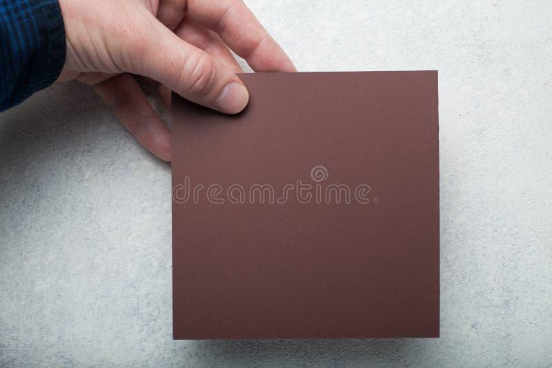 Pezzo di carta quadrato marrone in una mano europea su un fondo bianco d'annata fotografie stock