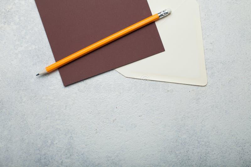 Pezzo di carta quadrato marrone vuoto, la busta beige e la matita su fondo bianco d'annata Spazio vuoto per testo fotografie stock libere da diritti