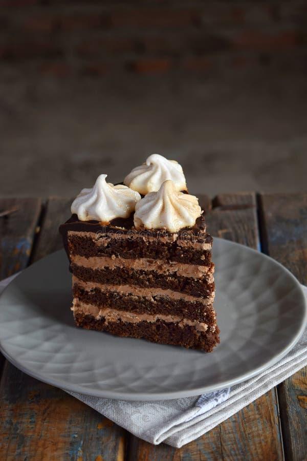Pezzo di dolce di cioccolato decorato con le rosette della crema della meringa: biscotto del cioccolato-dado, crema del caramello immagini stock