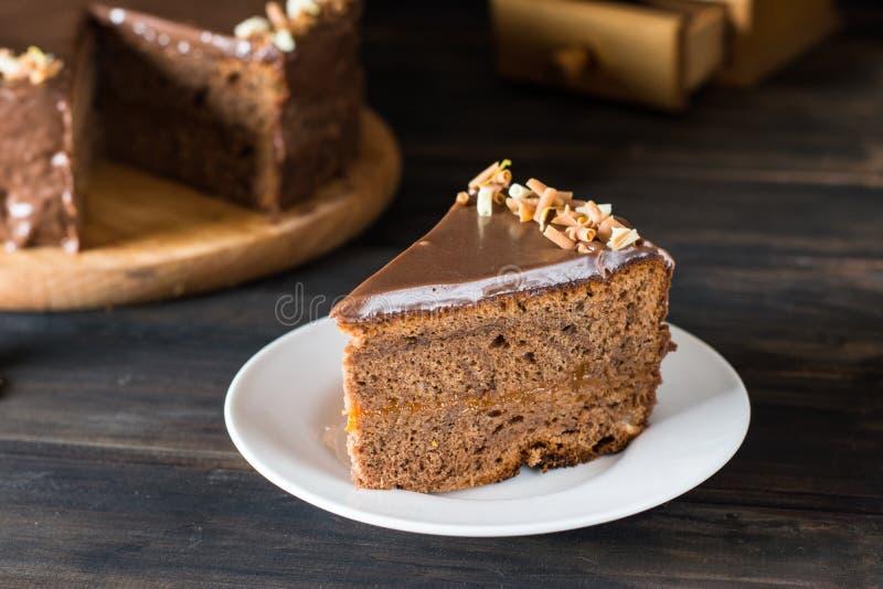 Pezzo di dolce di cioccolato su un piatto bianco su di legno Dolce austriaco tradizionale Dolce di Sacher Torta dell'albicocca Co fotografie stock libere da diritti