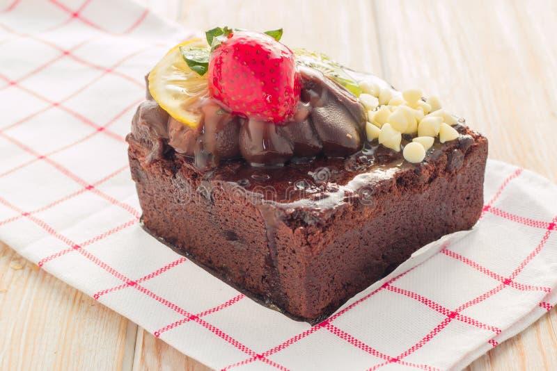 Pezzo di dolce di cioccolato con glassa e la bacca fresca sul BAC di legno immagine stock