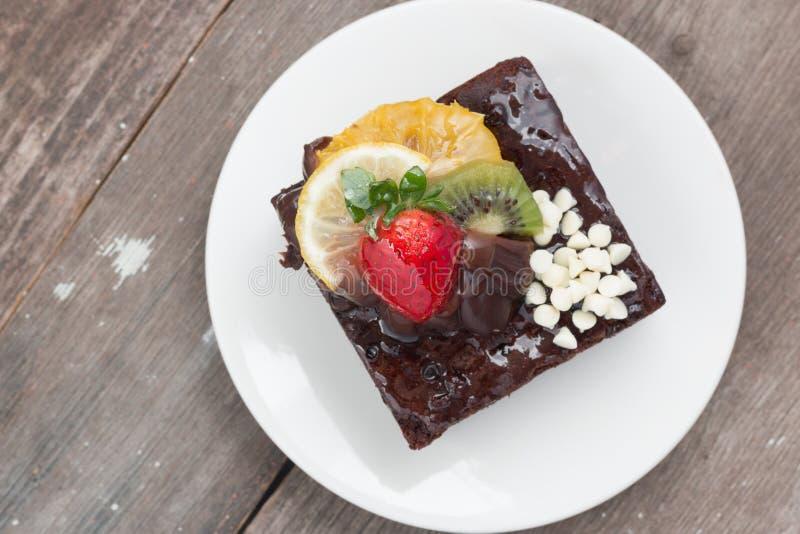 Pezzo di dolce di cioccolato con glassa e la bacca fresca sul BAC di legno fotografia stock