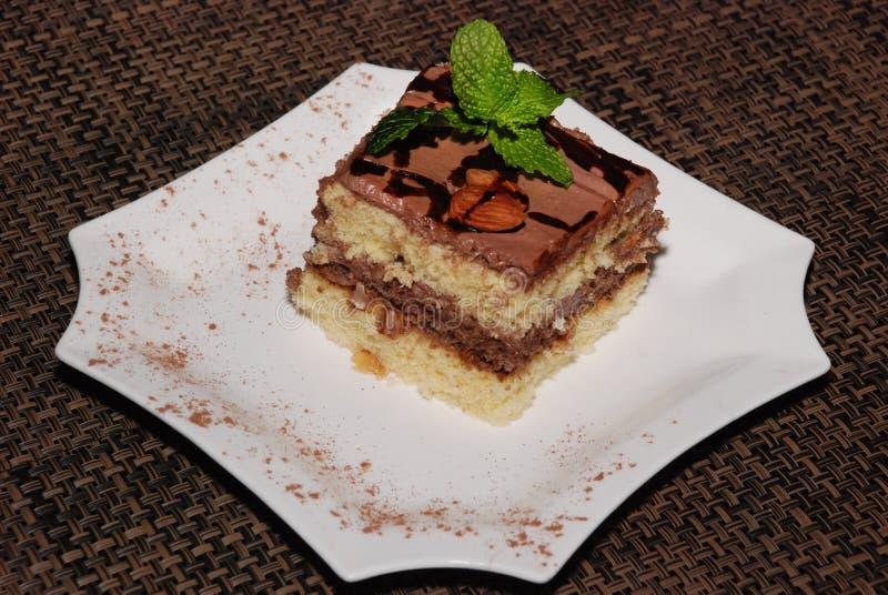 Pezzo di dolce quadrato con cioccolato e la mandorla sul piatto bianco fotografie stock