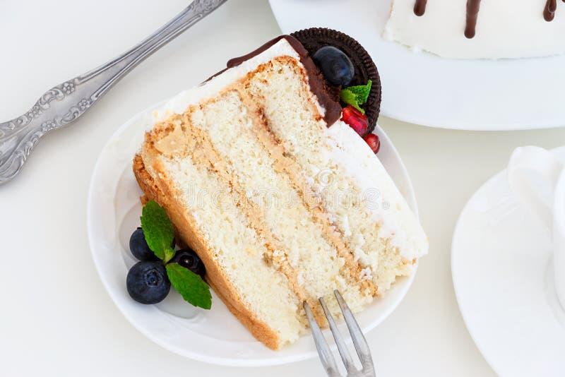 Pezzo di dolce di strato della vaniglia con il formaggio cremoso, del bacca ed i biscotti freschi del cioccolato immagine stock