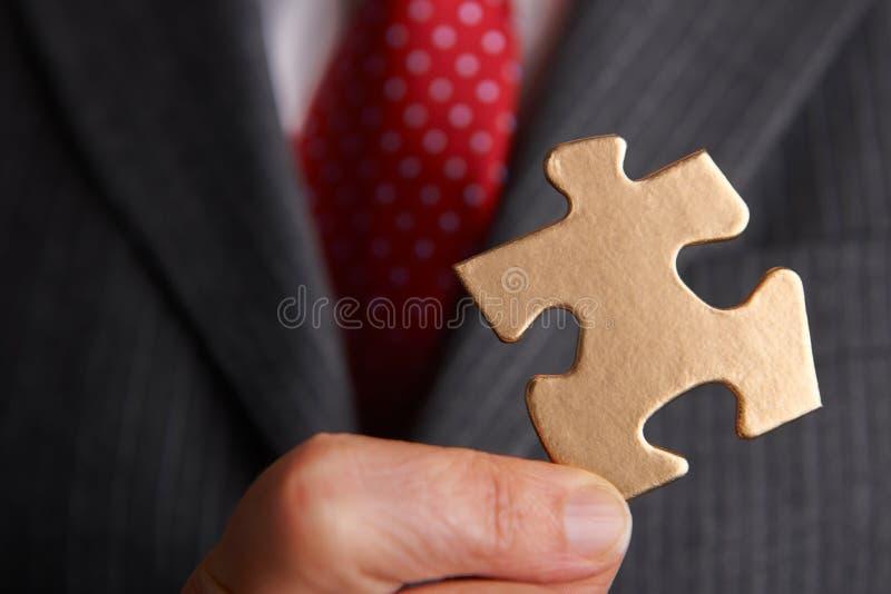 Pezzo di Holding Golden Jigsaw dell'uomo d'affari fotografia stock