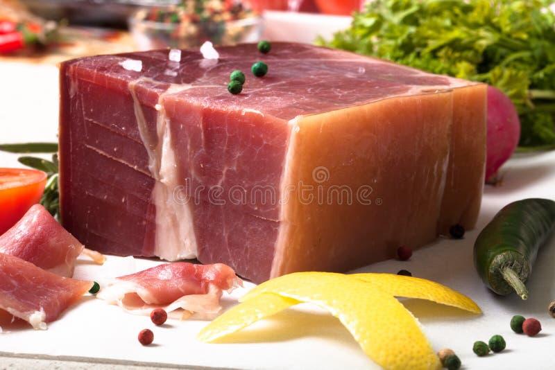 Pezzo di Jamon che si trova sulla tavola con le spezie fotografie stock libere da diritti