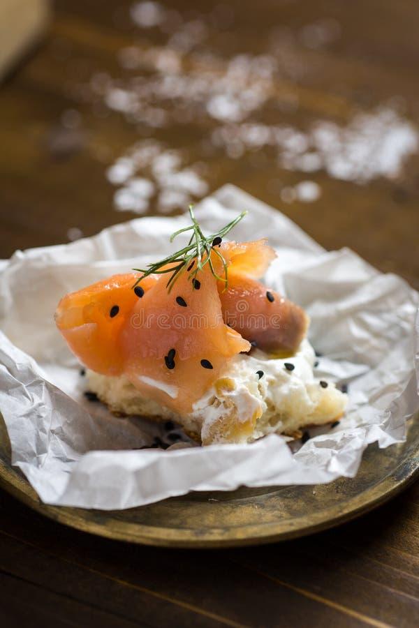 Pezzo di pane con il formaggio cremoso, del salmone affumicato, l'aneto fresco ed il sesamo nero fotografia stock libera da diritti