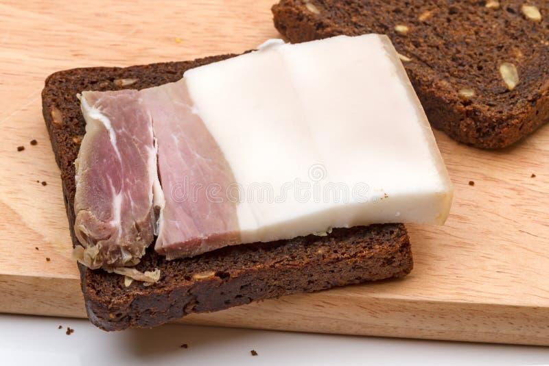 Pezzo di pane salato di segale e del bacon immagini stock libere da diritti