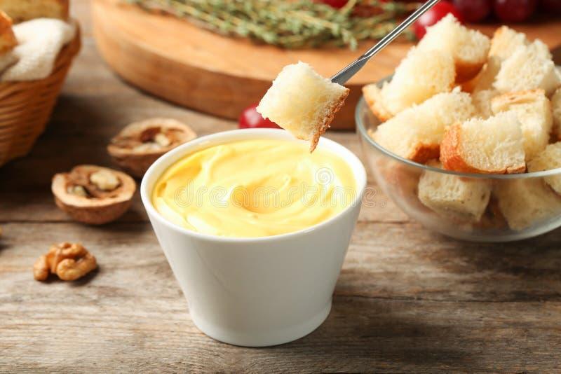 Pezzo di pane sopra la ciotola con la fonduta di formaggio deliziosa fotografia stock