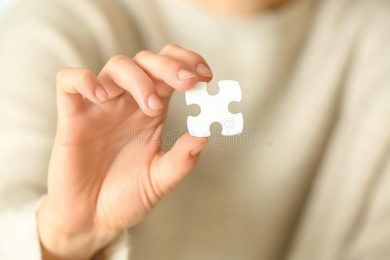 Pezzo di puzzle, primo piano della tenuta della donna immagini stock