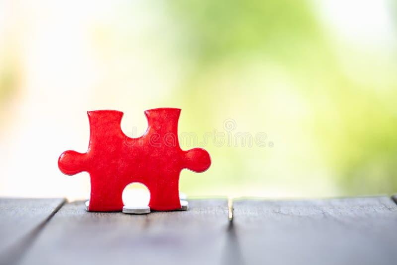 Pezzo di puzzle rosso sul vecchio legno e sui precedenti verdi Concetto di lavoro di squadra Simbolo dell'associazione e del coll immagini stock