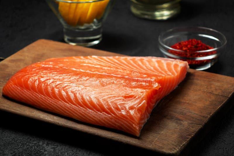 Pezzo di raccordo di color salmone su un tagliere di legno con gli ingredienti per sua ulteriore preparazione - foto, immagine immagine stock