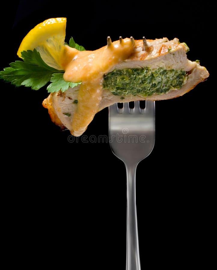 Pezzo di tacchino farcito con spinaci decorati con il limone ed il prezzemolo su una forcella fotografia stock